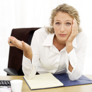 portrait of a young businesswoman sitting baffled at her desk
